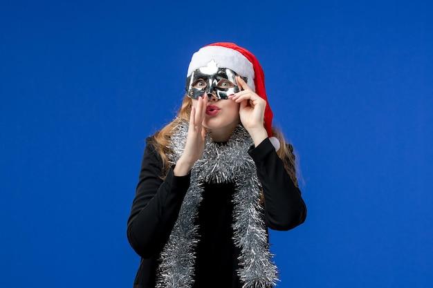 Widok z przodu młodej kobiety ze srebrną maską na niebieskiej ścianie