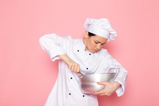 Widok z przodu młodej kucharki w białym garniturze kucharza w białej czapce przedstawiającej trzymającego srebrny rondel mieszający wnętrze