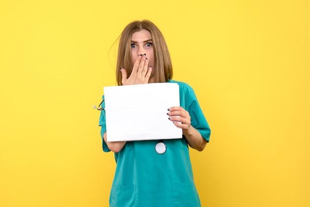 Widok z przodu młodej lekarki posiadającej pliki na żółtej ścianie