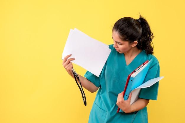 Widok z przodu młodej lekarki sprawdzania dokumentów stojących na żółtej ścianie
