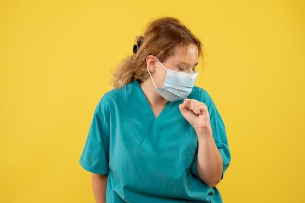 Widok z przodu młodej lekarki w garniturze i masce na żółtej ścianie