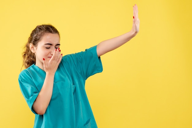 Widok z przodu młodej lekarki w garniturze na żółtej ścianie