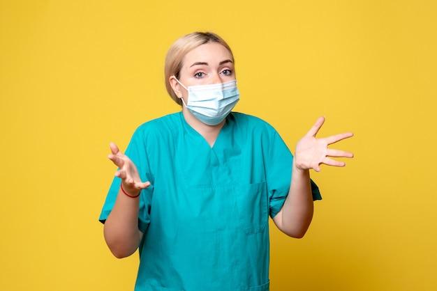 Widok z przodu młodej lekarki w koszuli medycznej i masce na żółtej ścianie