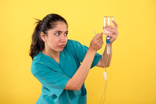 Widok z przodu młodej lekarki za pomocą surowicy na żółtej ścianie