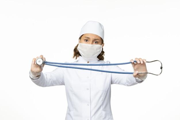 Widok z przodu młodej lekarki ze sterylną maską z powodu koronawirusa na jasnobiałej powierzchni