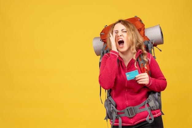 Widok z przodu młodej nerwowej dziewczyny podróżującej w masce medycznej, trzymając kartę bankową i dzwoniąc do kogoś