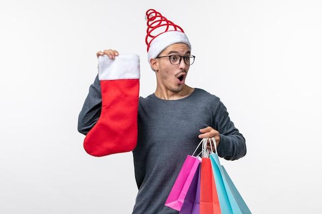 Widok z przodu młodej osoby po świątecznych zakupach na białej ścianie