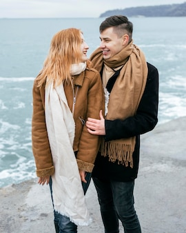 Widok z przodu młodej pary zimą przy plaży