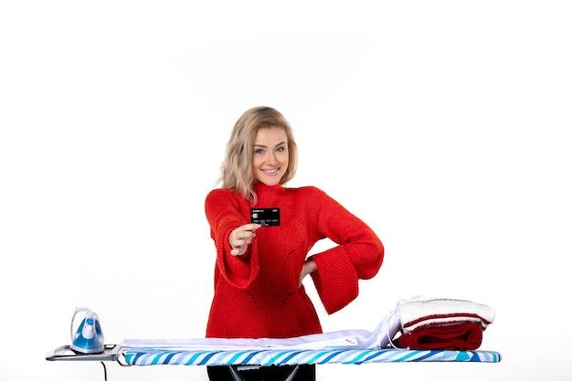 Widok z przodu młodej, pewnej siebie, zadowolonej, uśmiechniętej, atrakcyjnej kobiety stojącej za deską do prasowania pokazującą kartę bankową na białym tle