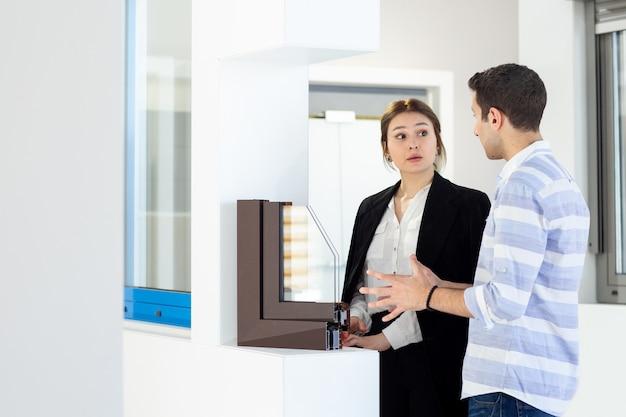 Widok z przodu młodej pięknej kobiety w ciemnych czarnych spodniach w białej koszuli i młodego mężczyzny omawiającego coś podczas wykonywania pracy w ciągu dnia