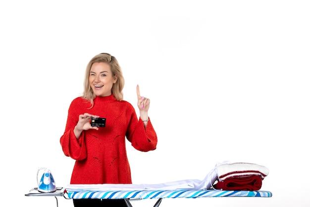 Widok z przodu młodej śmiesznej uśmiechniętej atrakcyjnej kobiety stojącej za deską do prasowania pokazującą kartę bankową skierowaną w górę po lewej stronie na białym tle