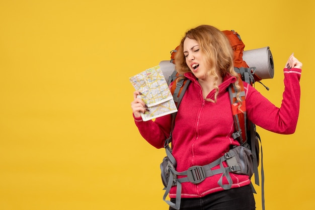 Widok z przodu młodej szczęśliwej dziewczyny podróżującej w masce medycznej, zbierającej bagaż i trzymając mapę, ciesząc się jej sukcesem