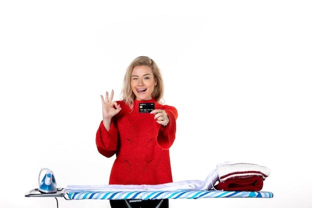 Widok z przodu młodej szczęśliwej emocjonalnej atrakcyjnej kobiety stojącej za deską do prasowania pokazującą kartę bankową wykonującą gest okularów na białym tle