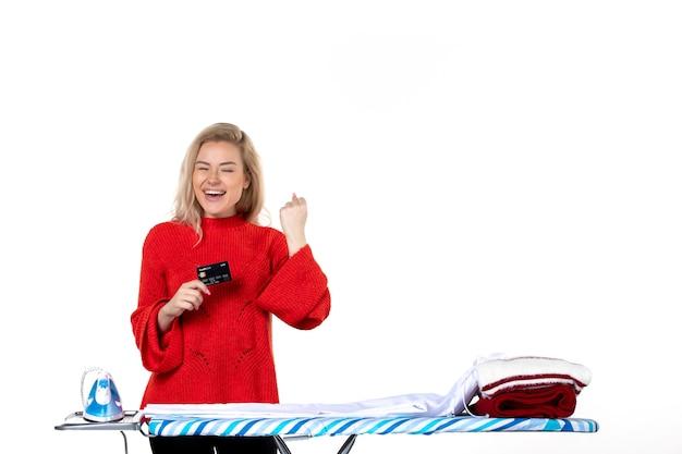 Widok z przodu młodej szczęśliwej uśmiechniętej atrakcyjnej kobiety stojącej za deską do prasowania pokazującej kartę bankową cieszącą się jej sukcesem na białym tle