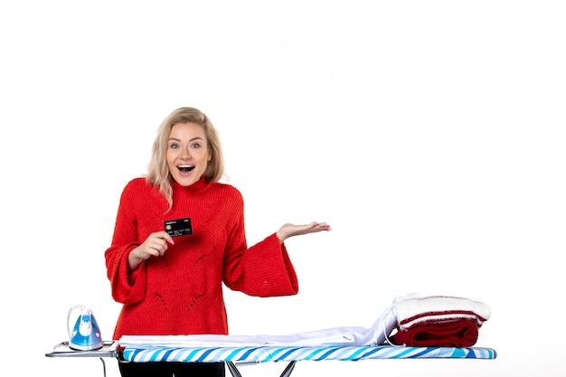 Widok z przodu młodej uśmiechniętej atrakcyjnej kobiety stojącej za deską do prasowania pokazującą kartę bankową wskazującą coś po lewej stronie na białym tle