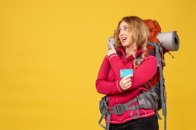 Widok z przodu młodej uśmiechniętej dziewczyny podróżującej w masce medycznej, zbierając swój bagaż trzymając kartę bankową