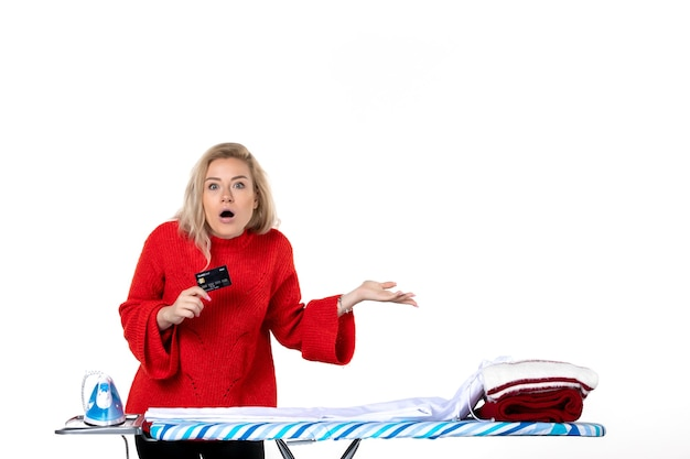 Widok z przodu młodej zaskoczonej atrakcyjnej kobiety stojącej za deską do prasowania pokazującej kartę bankową, która jest ciekawa czegoś na białym tle