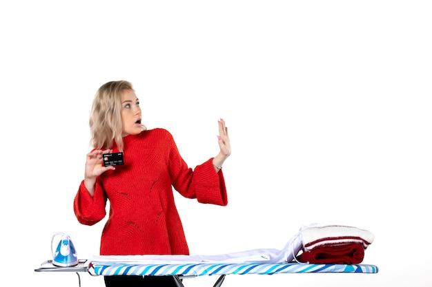 Widok z przodu młodej zaskoczonej atrakcyjnej kobiety stojącej za deską do prasowania pokazującej kartę bankową, która jest ciekawa czegoś po lewej stronie na białym tle
