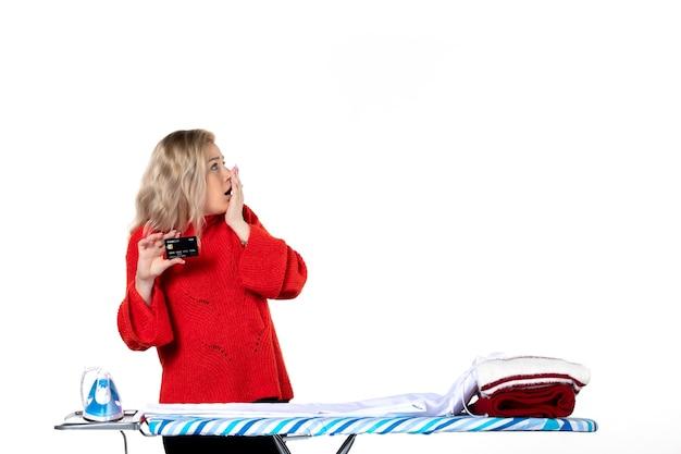Widok z przodu młodej zaskoczonej atrakcyjnej kobiety stojącej za deską do prasowania pokazującej kartę bankową patrzącą na coś po lewej stronie na białym tle