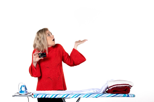 Widok z przodu młodej zaskoczonej atrakcyjnej kobiety stojącej za deską do prasowania pokazującej kartę bankową patrzącą w górę po lewej stronie na białym tle
