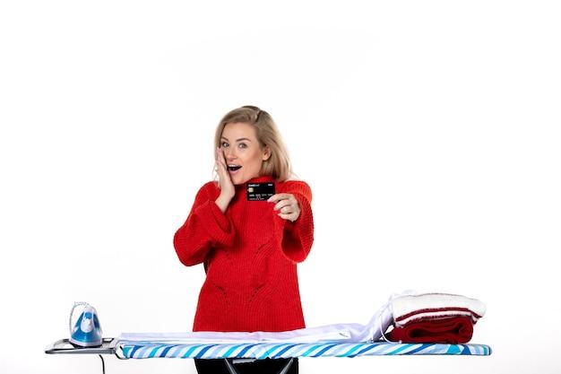 Widok z przodu młodej zaskoczonej uśmiechniętej atrakcyjnej kobiety stojącej za deską do prasowania pokazującą kartę bankową na białym tle