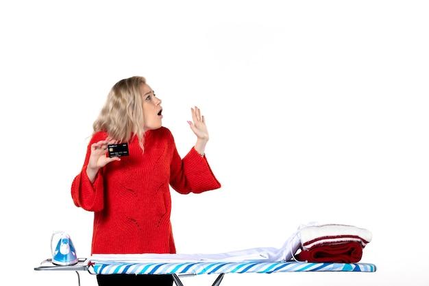 Widok z przodu młodej zszokowanej atrakcyjnej kobiety stojącej za deską do prasowania pokazującą kartę bankową, która jest ciekawa czegoś po lewej stronie na białym tle