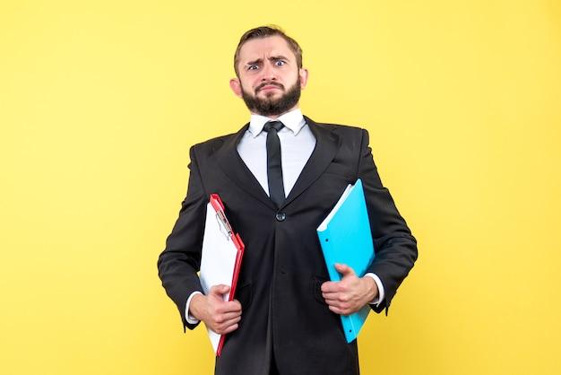 Widok z przodu młody biznesmen gospodarstwa foldery z zakłopotaną twarzą na żółto