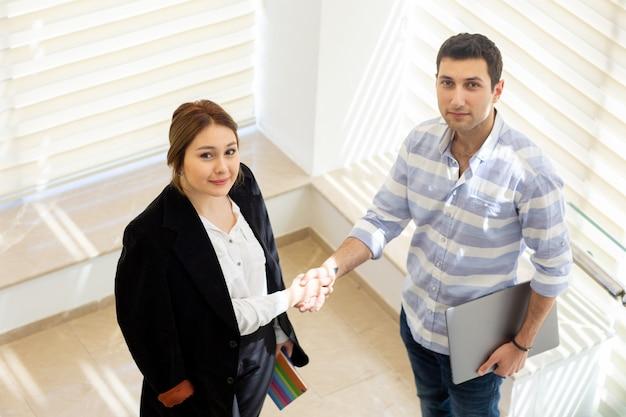 Widok z przodu młody biznesmen w pasiastej koszuli wraz z młodą damą biznesową omawiającą kwestie pracy, rozmawiającą podczas budowania aktywności w ciągu dnia