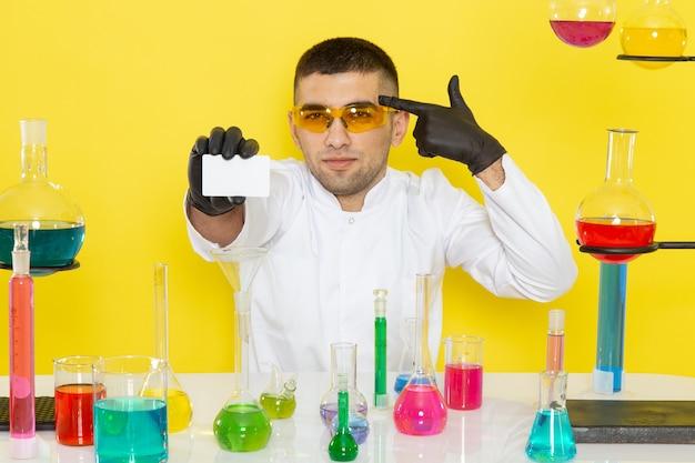 Widok z przodu młody chemik mężczyzna w białym garniturze przed stołem z kolorowymi roztworami, trzymając białą kartkę na żółtej ścianie