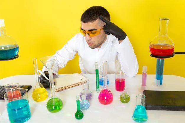 Widok z przodu młody chemik mężczyzna w białym garniturze przed stołem z kolorowymi roztworami zapisującymi notatki na jasnym stole praca naukowa laboratorium chemia