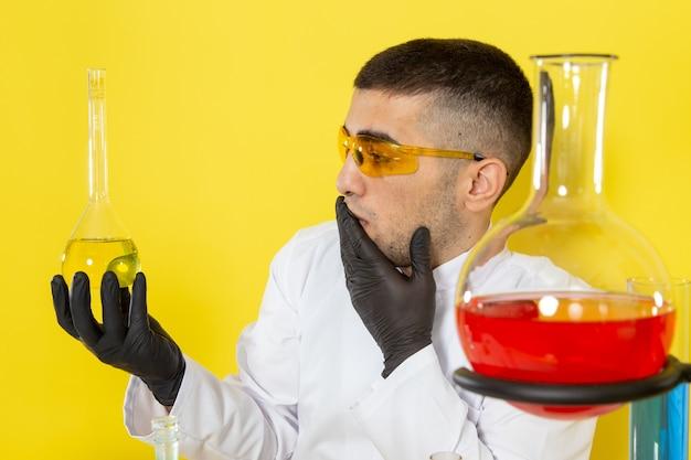 Widok z przodu młody chemik mężczyzna w białym specjalnym garniturze przed stołem z kolorowymi roztworami trzymający kolbę zaskoczony na żółtym biurku praca naukowa laboratorium chemiczne