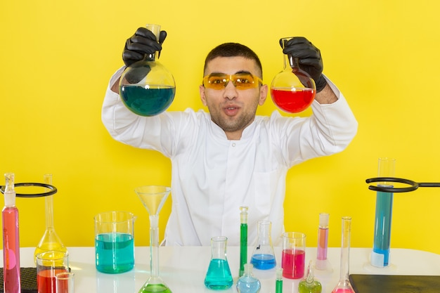 Widok z przodu młody chemik mężczyzna w białym specjalnym garniturze przed stołem z kolorowymi roztworami trzymającymi kolby na żółtym biurku praca naukowa laboratorium chemiczne
