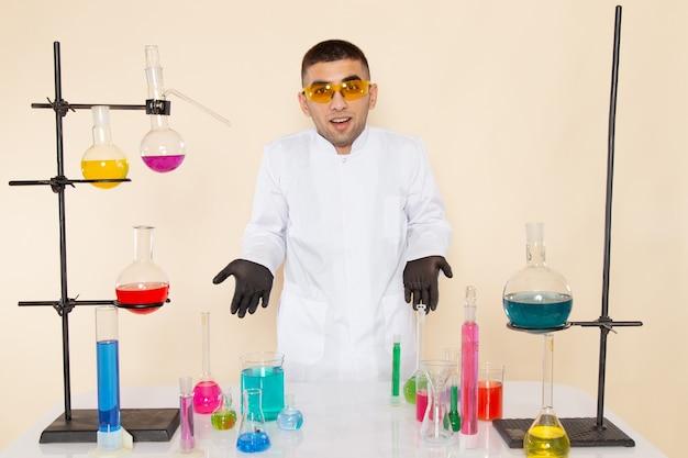Widok z przodu młody chemik mężczyzna w białym specjalnym garniturze przed stołem z roztworami pozującymi na kremowej ścianie laboratorium nauki chemii