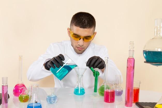Widok z przodu młody chemik mężczyzna w białym specjalnym garniturze siedzi przed stołem z roztworami mieszającymi je na kremowej ścianie laboratorium nauki chemii