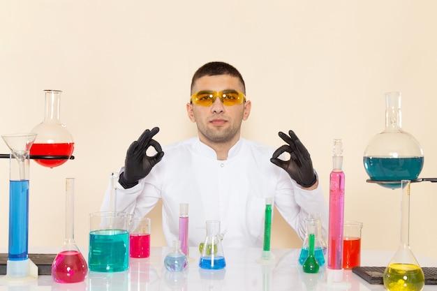 Widok z przodu młody chemik mężczyzna w białym specjalnym garniturze siedzi przed stołem z roztworami na kremowej ścianie laboratorium eksperyment naukowy chemii