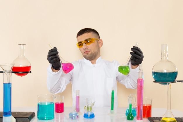 Widok z przodu młody chemik mężczyzna w białym specjalnym garniturze siedzi przed stołem z roztworami, trzymając na kremowej ścianie laboratorium chemii eksperyment naukowy