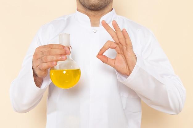Widok z przodu młody chemik mężczyzna w białym specjalnym garniturze trzyma kolbę z żółtym roztworem na ścianie kremu laboratorium naukowe eksperyment chemia naukowa
