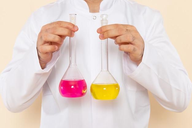 Widok z przodu młody chemik mężczyzna w białym specjalnym garniturze trzymający kolby z żółtymi różowymi roztworami na kremowej ścianie laboratorium naukowe eksperyment chemia naukowa