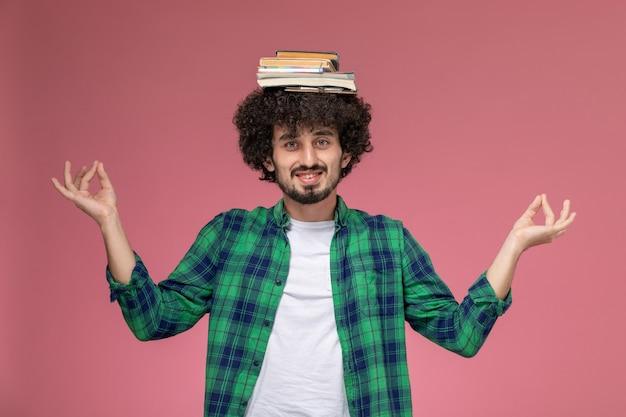 Widok z przodu młody chłopak kładąc swoje książki na głowie