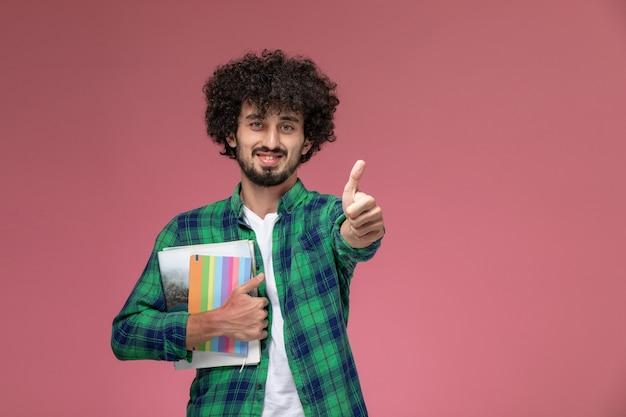 Widok z przodu młody chłopak pokazując kciuki do góry z różnymi notebookami