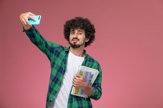 Widok z przodu młody człowiek, biorąc selfie i patrząc na kamery