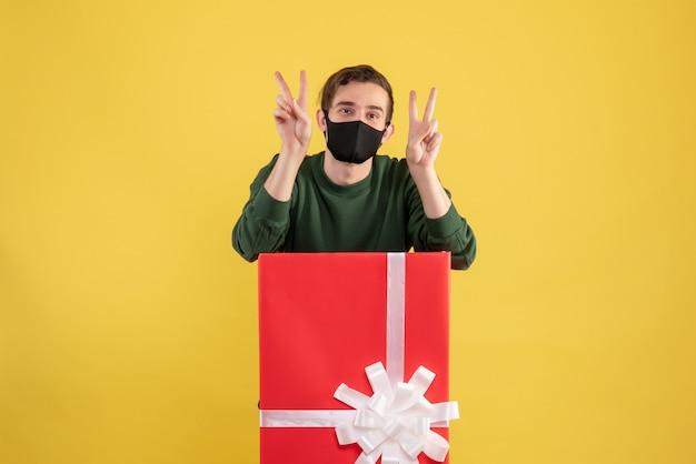 Widok z przodu młody człowiek co znak zwycięstwa stojący za dużym pudełkiem na prezenty na żółto