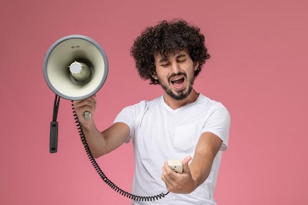 Widok z przodu młody człowiek jest zły z ręcznym mikrofonem