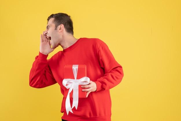 Widok z przodu młody człowiek krzyczy na żółtym tle z czerwonym swetrem