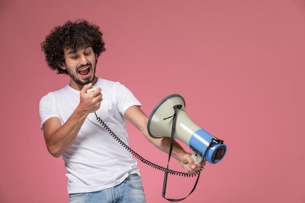 Widok z przodu młody człowiek krzyczy z ręcznym mikrofonem