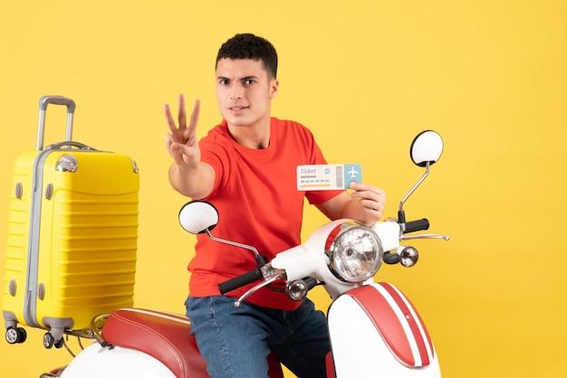 Widok z przodu młody człowiek na motorowerze posiadający bilet pokazujący trzy palce