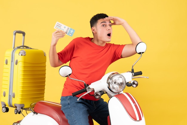 Widok z przodu młody człowiek na motorowerze trzymając bilet obserwując