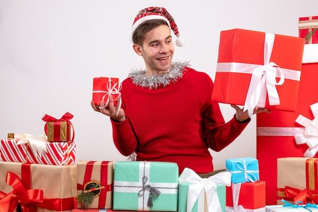 Widok z przodu młody człowiek patrząc na prezenty siedząc wokół świątecznych prezentów