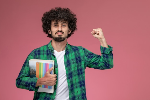 Widok z przodu młody człowiek pokazujący swoją siłę z notebookami