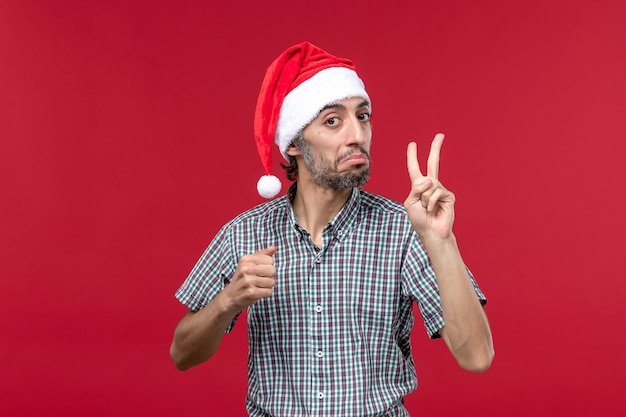 Widok z przodu młody człowiek pokazuje numer na czerwonej ścianie wakacje nowy rok mężczyzna czerwony